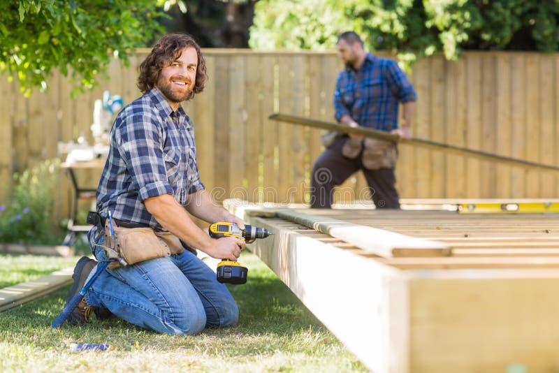 Madeira segura da perfuração do trabalhador na construção fotos de stock royalty free
