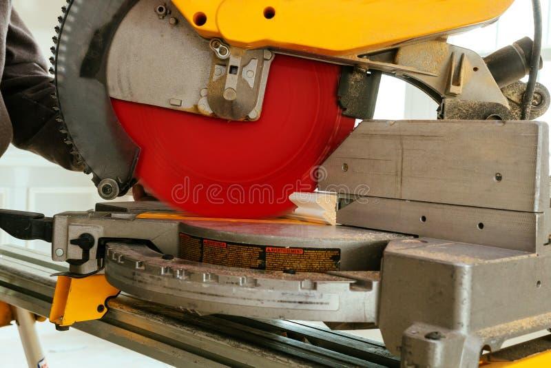 A madeira serrada madura do sawing de Closeupof com deslizamento da mitra composta viu, voo da serragem ao redor imagem de stock royalty free