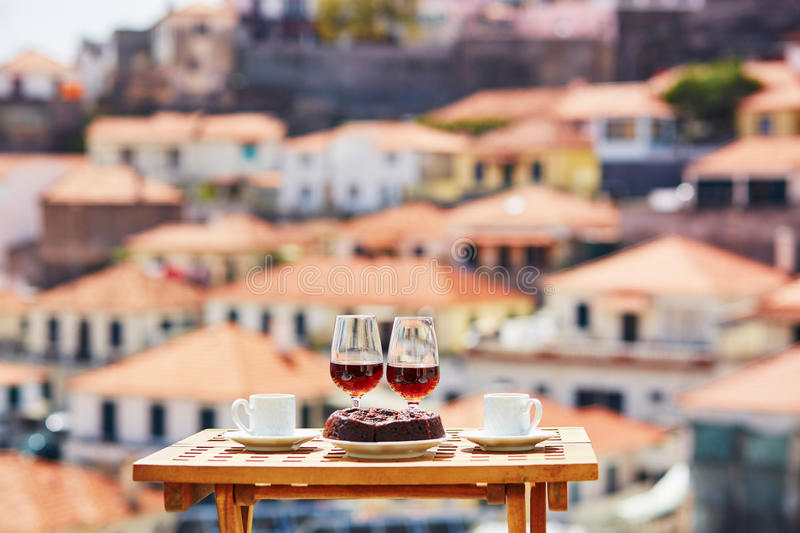 Madeira wine, coffee and bolo de mel with view to Funchal, Madeira, Portugal. Two glasses of Madeira wine, two cups of fresh espresso coffee and traditional stock image