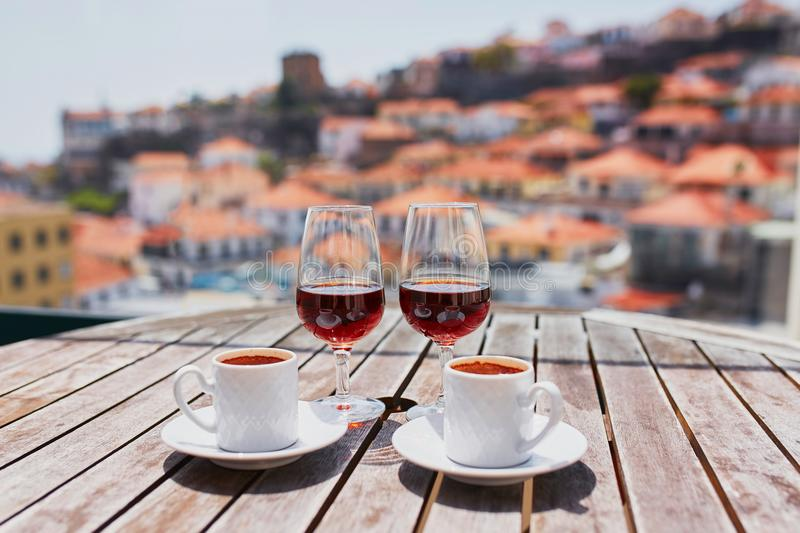 Madeira wine, coffee and hohey cake, View to Funchal, Portugal. Two glasses of Madeira wine and two cups of fresh espresso coffee in street cafe with view to stock image