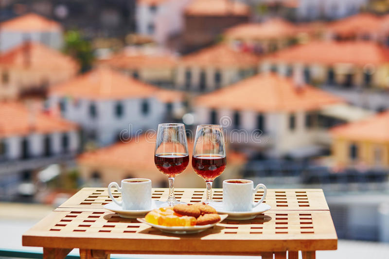 Madeira wine, coffee and sweets with view to Funchal, Madeira, Portugal. Two glasses of Madeira wine, two cups of fresh espresso coffee and traditional royalty free stock photography