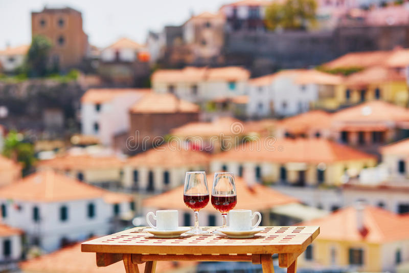 Madeira wine and coffee with view to Funchal, Madeira, Portugal. Two glasses of Madeira wine and two cups of fresh espresso coffee in cafe with view to Funchal royalty free stock photo