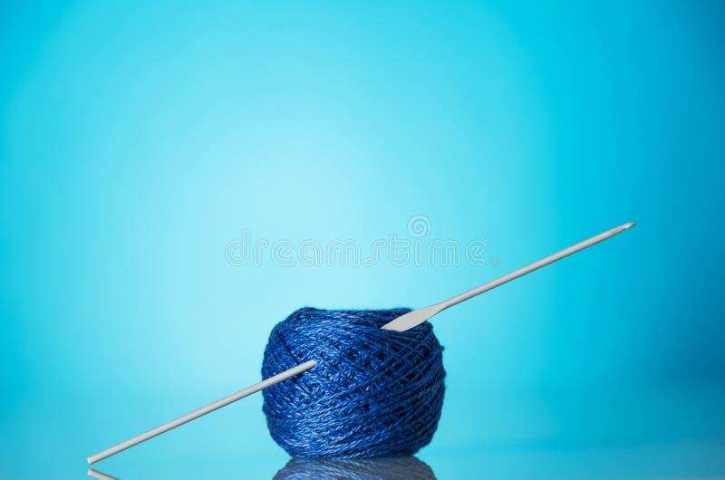 Madeja del hilado de lanas azul para las agujas que hacen punto y que hacen punto en fondo azul brillante fotografía de archivo