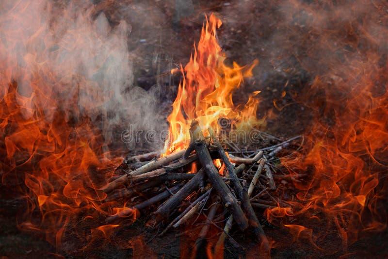 Madera ardiente en la noche Hoguera en el campo turístico en la naturaleza en montañas Chispas del fuego del amd de la llama en f imagenes de archivo