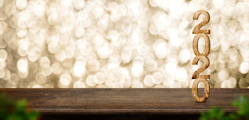 Madera de la Feliz Año Nuevo 2020 con la estrella chispeante en la tabla de madera marrón con el fondo del bokeh del oro, concept fotografía de archivo libre de regalías