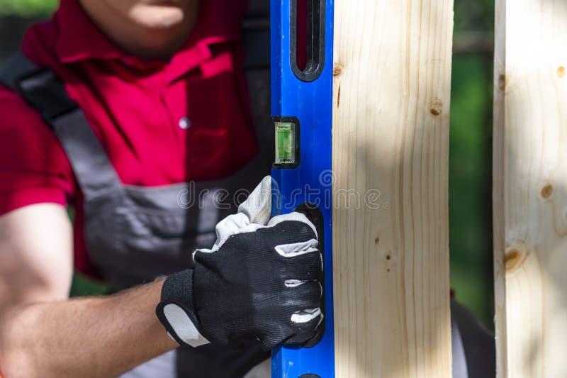 Madera de medición del carpintero joven usando nivel de alcohol del agua en su trabajo foto de archivo