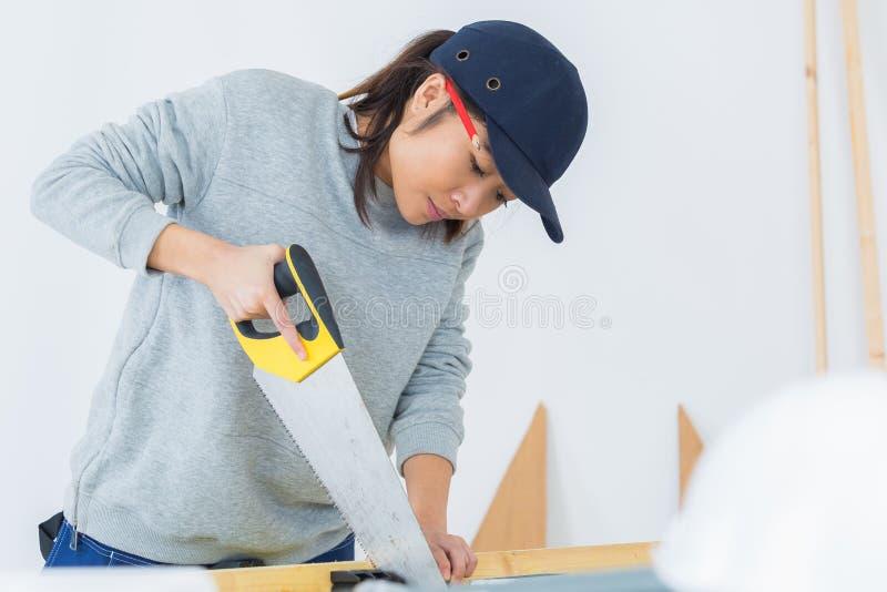 Madera femenina joven concentrada del corte del carpintero fotografía de archivo