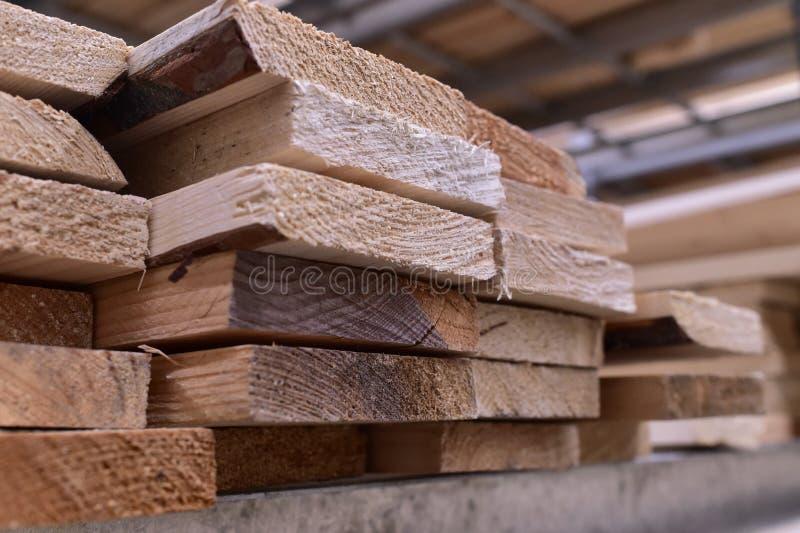 Madera, tableros no previstos del pino apilados encima de uno a en el estante del metal fotografía de archivo