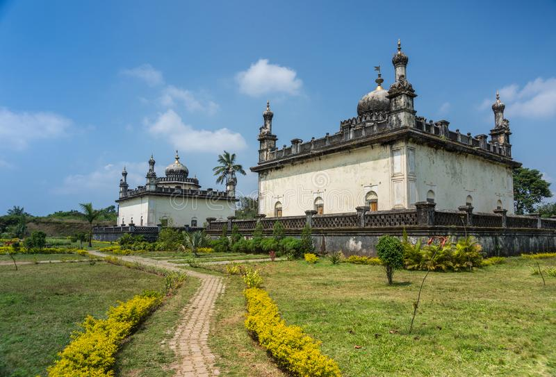 Two Royal mausoleum at domain Raja Tombs, Madikeri India. Madikeri, India - October 31, 2013: Two largest white and gray Royal mausoleum set in green garden of stock photo
