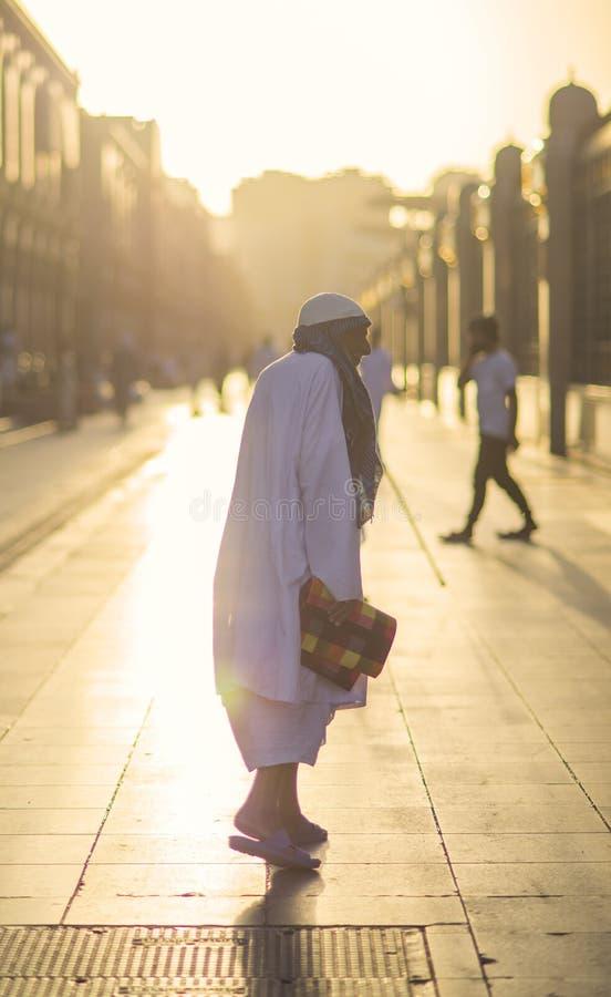 Madina, arabischer Saudi, am 20. März 2016: Alter Mann nach Gebetsweg im Korridor mit Reflexion des Sonnenuntergangs lizenzfreies stockbild