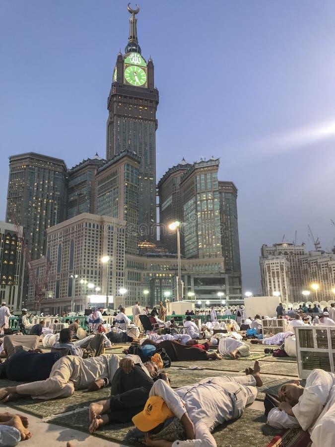 MADINA, REINO do SAUDITA ARÁBIA 31 DE MAIO DE 2019: Um grupo de peregrinos muçulmanos toma um resto após a oração da manhã do faj fotografia de stock