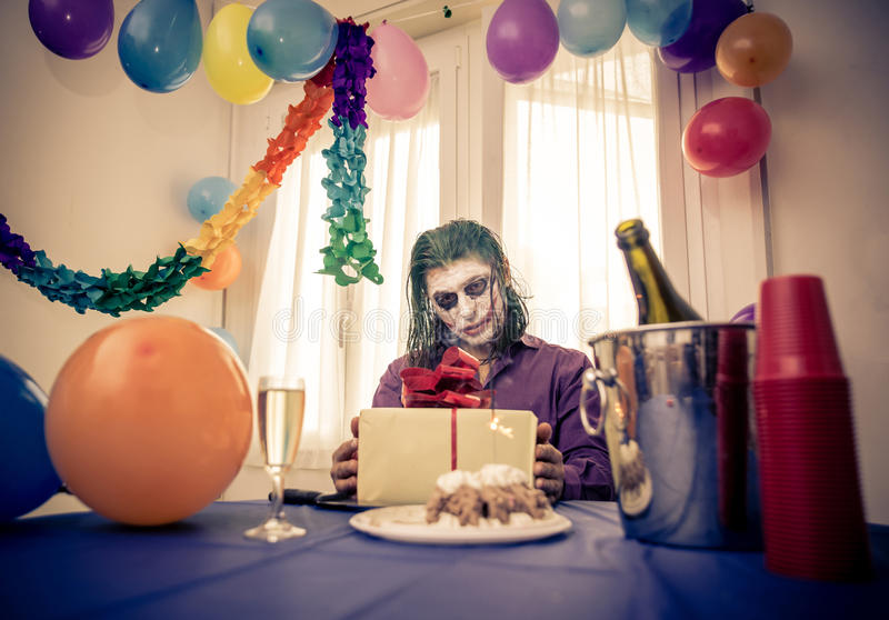 Madness party. Sad clown sitting alone at his birthday party royalty free stock images
