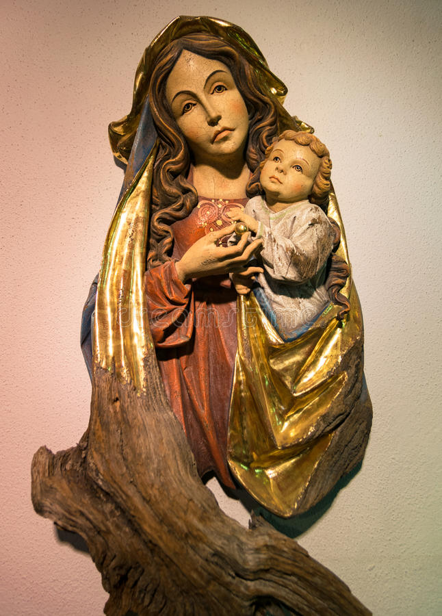 Download Madonna With Child Carved In A Wooden Stem. Editorial Stock Photo - Image: 83723973