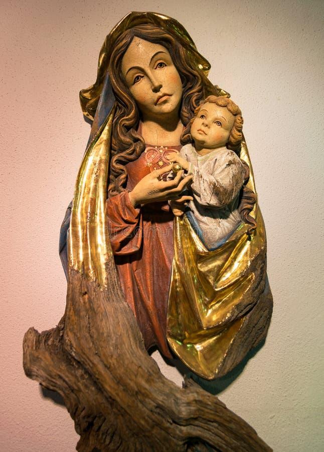 Madonna com criança cinzelou em uma haste de madeira fotos de stock