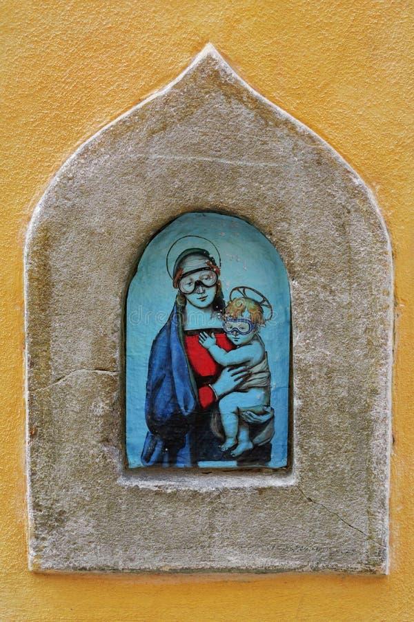 Madonna y el niño en máscaras que se zambullen - arte moderno de la calle en el vino medieval Buchette porta del vino fotografía de archivo libre de regalías