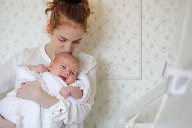 Madre abbastanza giovane che tiene una figlia neonata in armi immagine stock libera da diritti