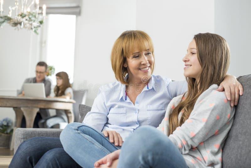 madre affettuosa e figlia che si siedono sul sofà con la famiglia nel fondo immagini stock libere da diritti
