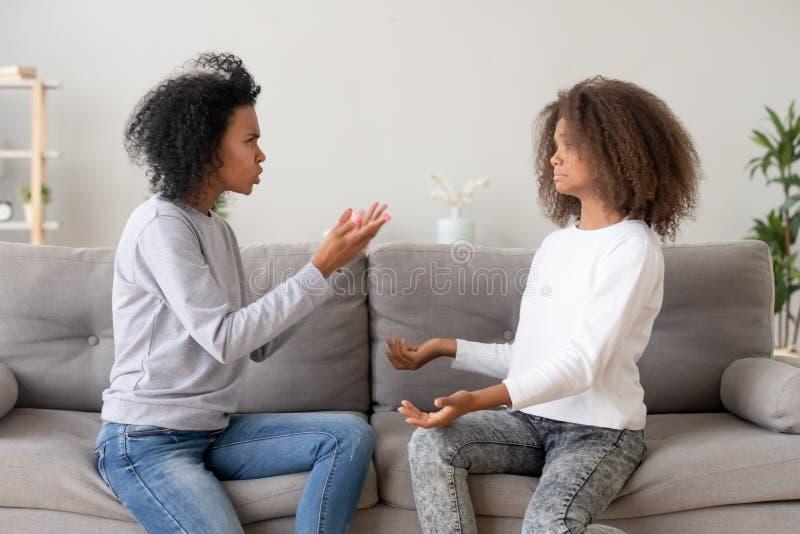 Madre africana que regaña a la hija adolescente que se sienta en el sofá en casa foto de archivo libre de regalías
