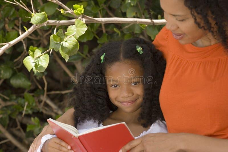 Madre afroamericana e la sua lettura del daugher immagine stock libera da diritti