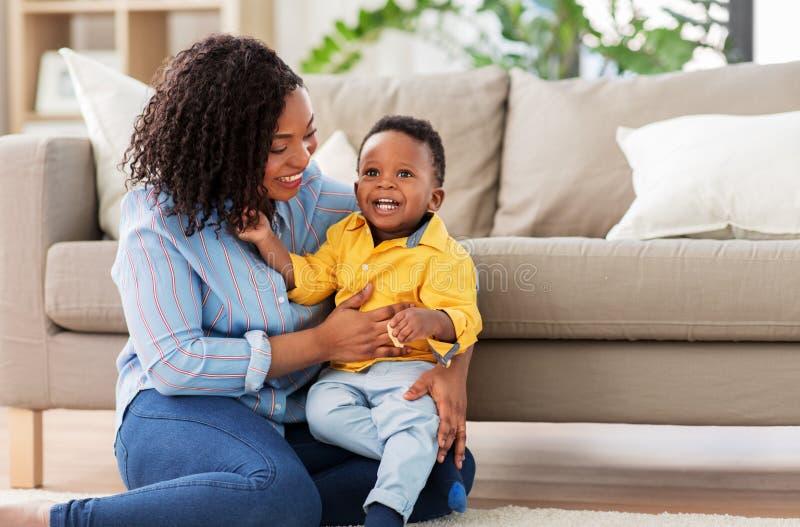 Madre afroamericana feliz con el beb? en casa fotos de archivo