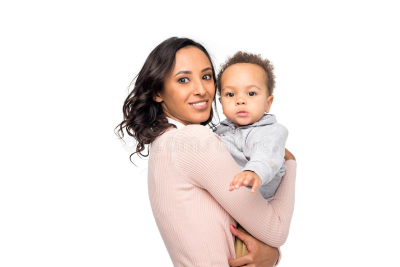 madre afroamericana feliz que lleva al pequeño niño adorable y que mira la cámara imagen de archivo