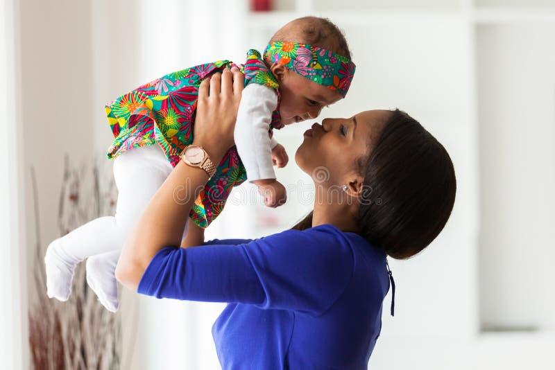 Madre afroamericana joven que juega con su bebé