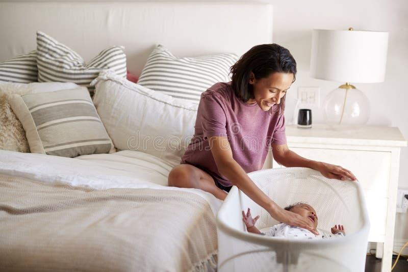 Madre afroamericana millenaria che si siede sul suo letto che conforta il suo lato del letto di menzogne gridante del bambino lei fotografie stock