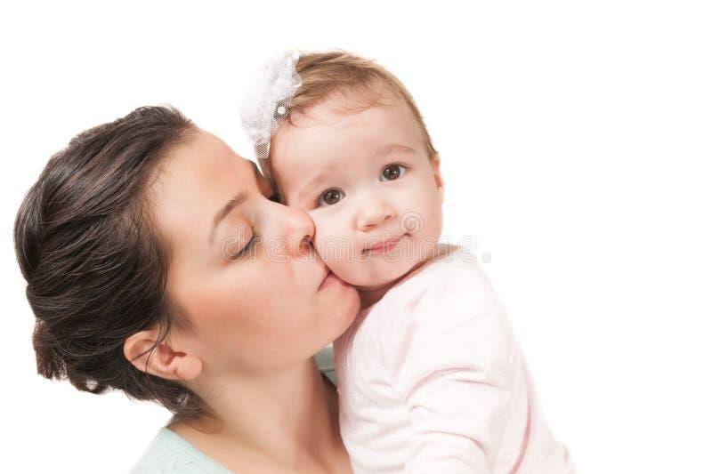 Madre aislada que besa a su niña en el fondo blanco imágenes de archivo libres de regalías