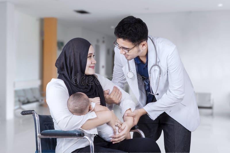 Madre aiutata da medico nell'ingresso dell'ospedale immagini stock