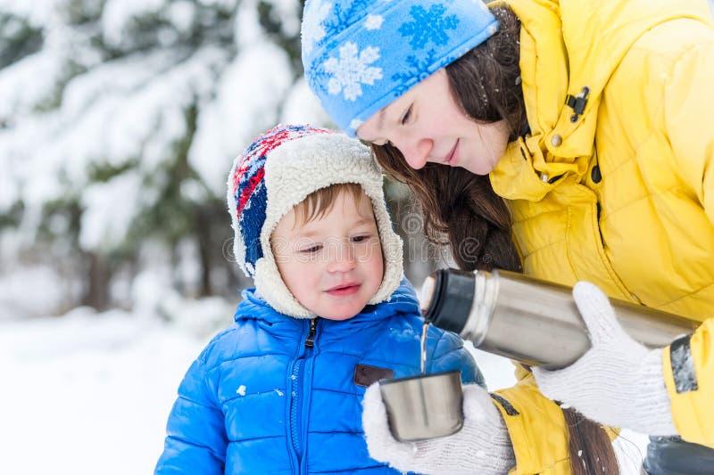 Madre al aire libre y niño del retrato que beben té caliente de un termo imagenes de archivo