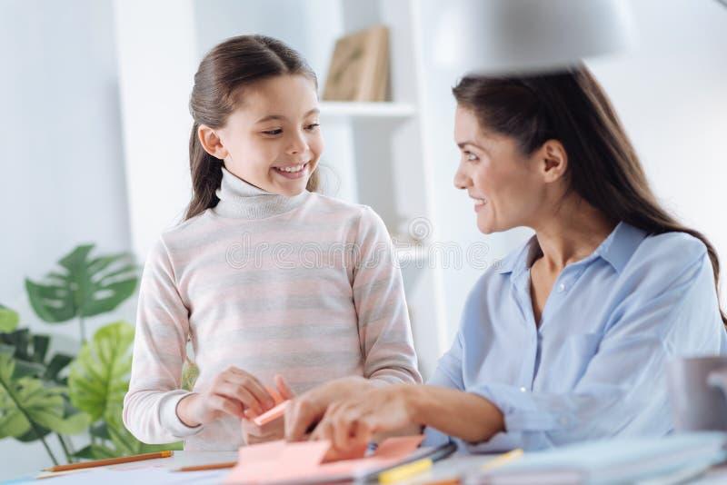 Madre alegre e hija que estudian junto imagen de archivo libre de regalías