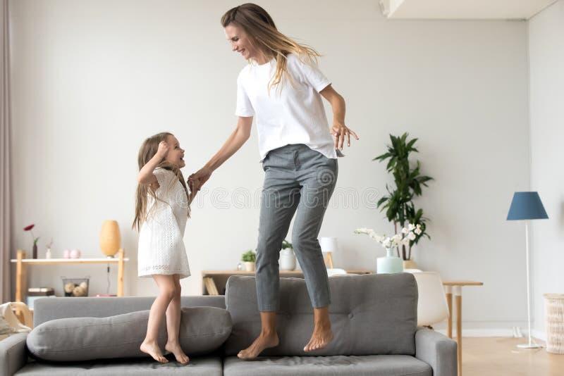 Madre alegre e hija que saltan en el sofá en casa fotos de archivo