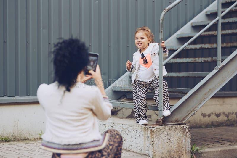 Madre alegre e hija que se divierten en ciudad Una madre joven fotografía a su hija en un teléfono móvil Niño que presenta para imágenes de archivo libres de regalías
