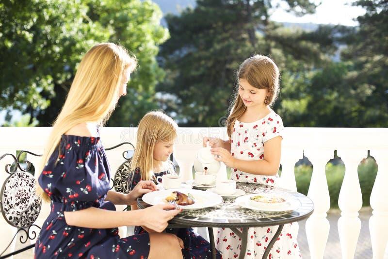 Madre alegre e hija que se sientan en el café del aire libre mientras que drin imagen de archivo