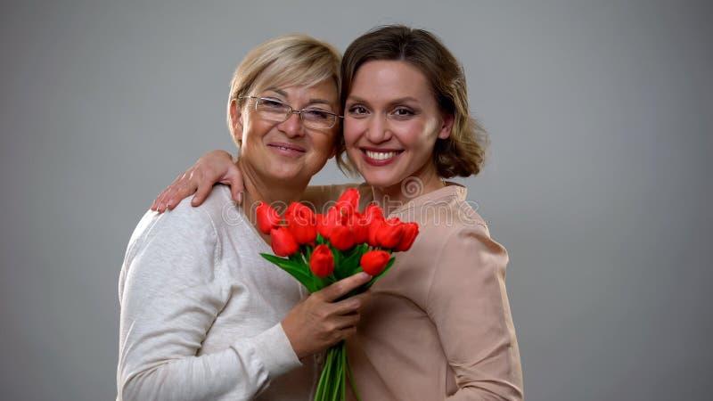 Madre alegre e hija que sonríen y que miran la cámara, sosteniendo tulipanes fotos de archivo libres de regalías