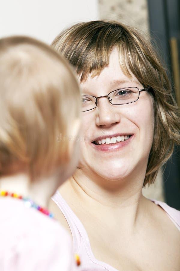 Madre alegre radiante que mira a la pequeña hija foto de archivo libre de regalías