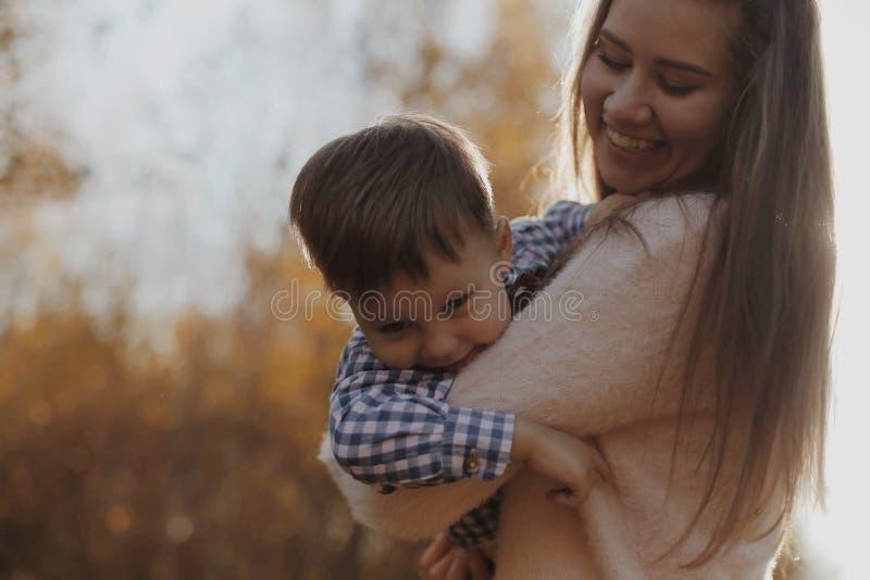 Madre allegra che si tiene per mano e che fila suo figlio nel ragazzo felice della foresta divertendosi con sua madre fotografia stock