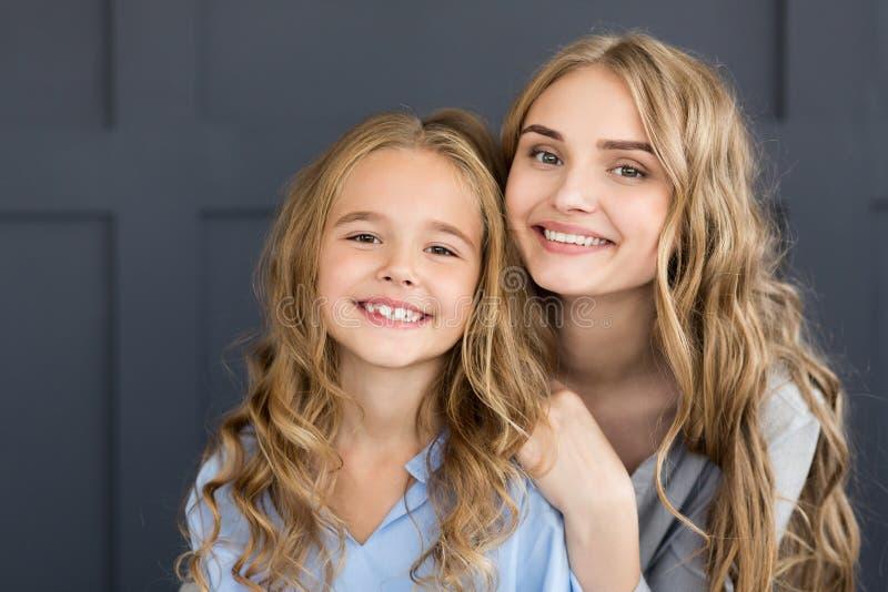Madre allegra e figlia che sorridono alla macchina fotografica fotografie stock libere da diritti