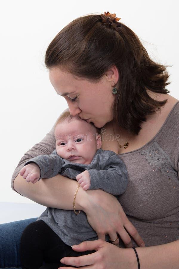 Madre amorosa che bacia il suo bambino isolato su fondo bianco fotografie stock