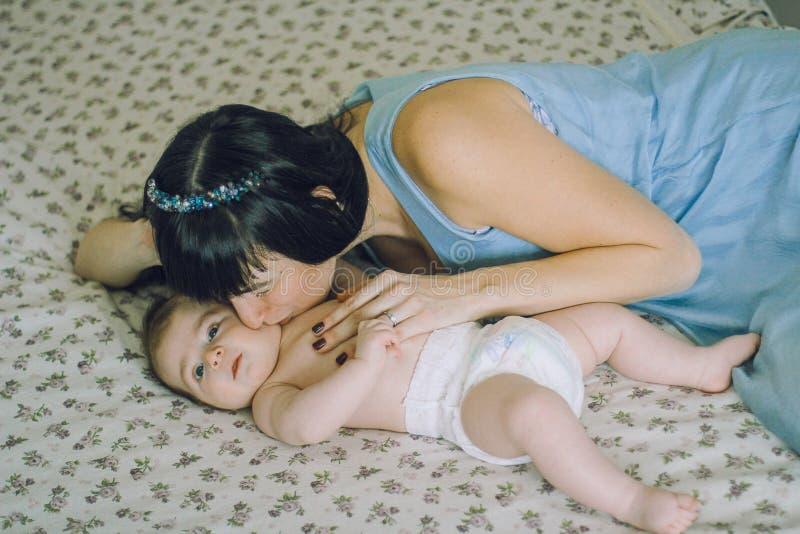 Madre amorosa con il suo piccolo bambino sul letto fotografia stock libera da diritti