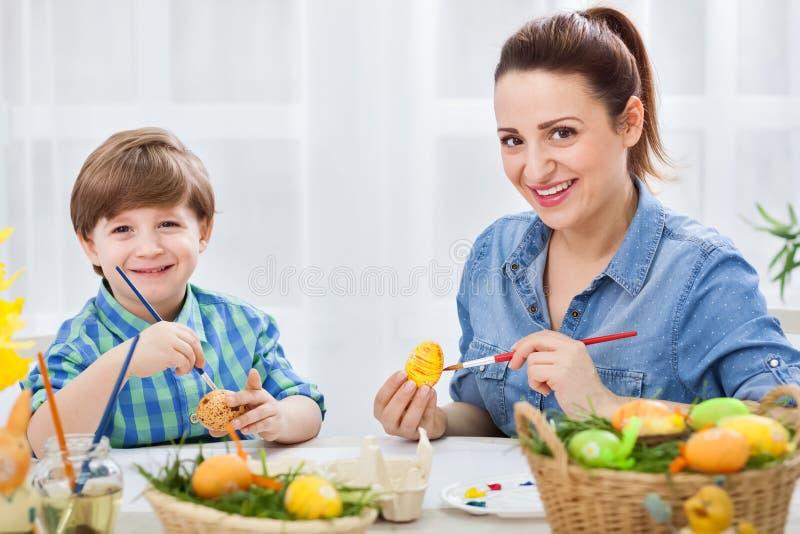 Madre amorosa e suo il bambino che dipingono le uova di Pasqua immagine stock libera da diritti