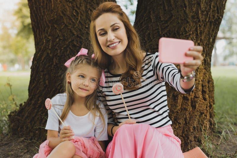 Madre amorosa moderna che fa selfie con la figlia sveglia immagine stock