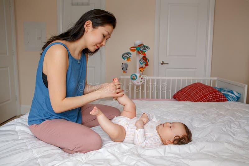 Madre asiática de la raza mixta con el bebé recién nacido que hace masaje y ejercicios físicos imagen de archivo