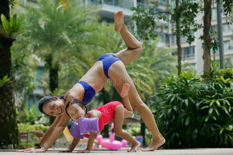 Madre asiática e hija chinas que hacen yoga en la piscina feliz imagen de archivo
