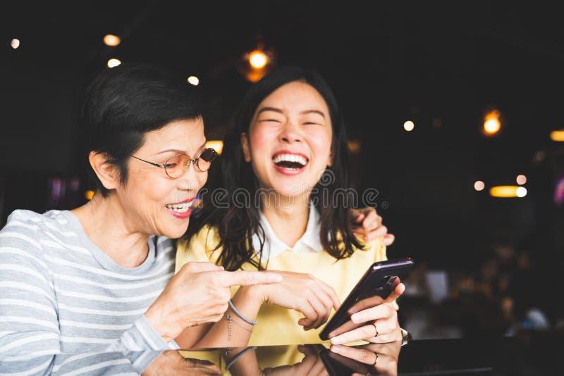 Madre asiática e hija que ríen y que sonríen en un álbum del selfie o de foto, usando smartphone junto en el restaurante o el caf fotografía de archivo