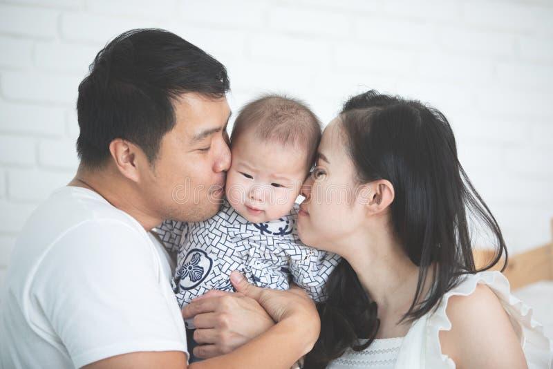 Madre asiática feliz del padre de la familia con la hija que se besa con el smil fotografía de archivo
