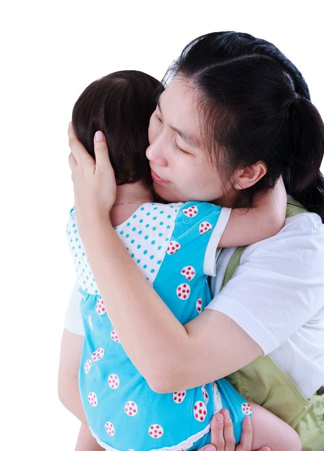 Madre asiática feliz que lleva a su hija Aislado en la parte posterior del blanco fotos de archivo