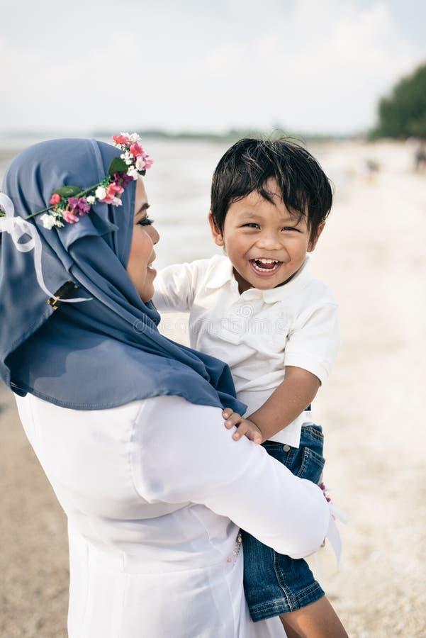 Madre asiática joven cariñosa que celebra a su hijo que sonríe y que se ríe de la playa imagen de archivo libre de regalías