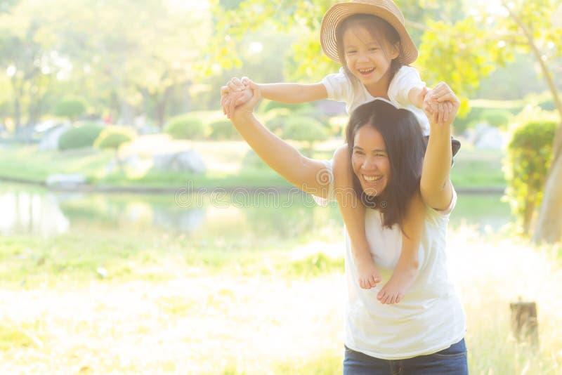 Madre asi?tica joven hermosa que lleva a poca hija con la sonrisa, paseo del ni?o el cuello en mam? con felicidad y alegre imagen de archivo libre de regalías