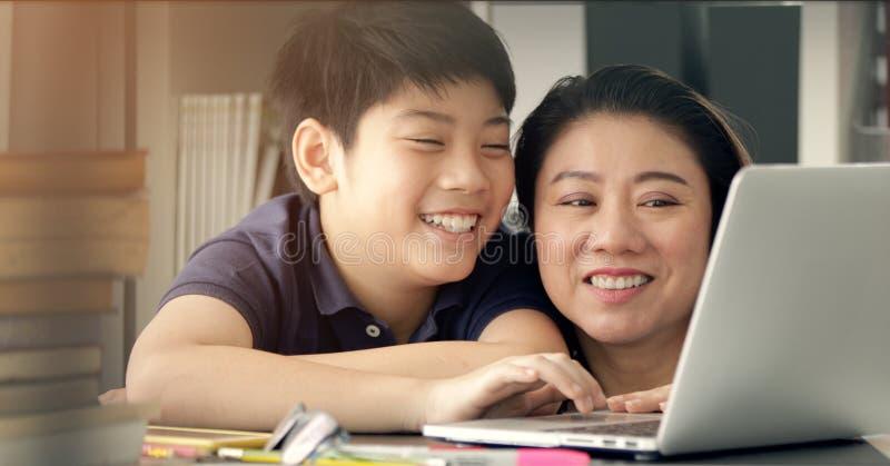 Madre asiática linda que ayuda a su hijo que hace su preparación foto de archivo libre de regalías